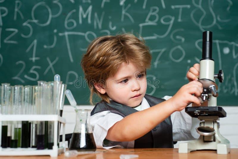 La salle de classe de la science Peu scientifique d'enfant gagnant la chimie dans le laboratoire d'?cole Le?on de biologie L'enfa images stock