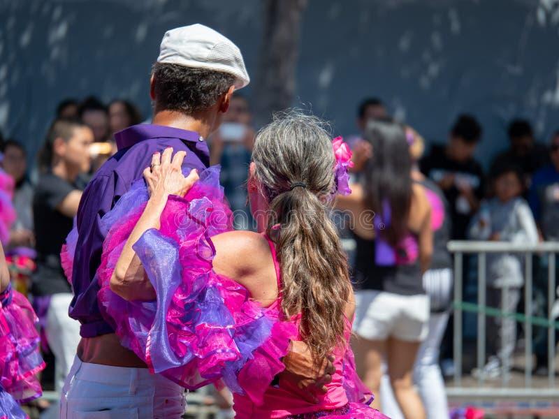 La salsa del hombre y de la mujer baila en el medio de un desfile con una muchedumbre imagen de archivo libre de regalías