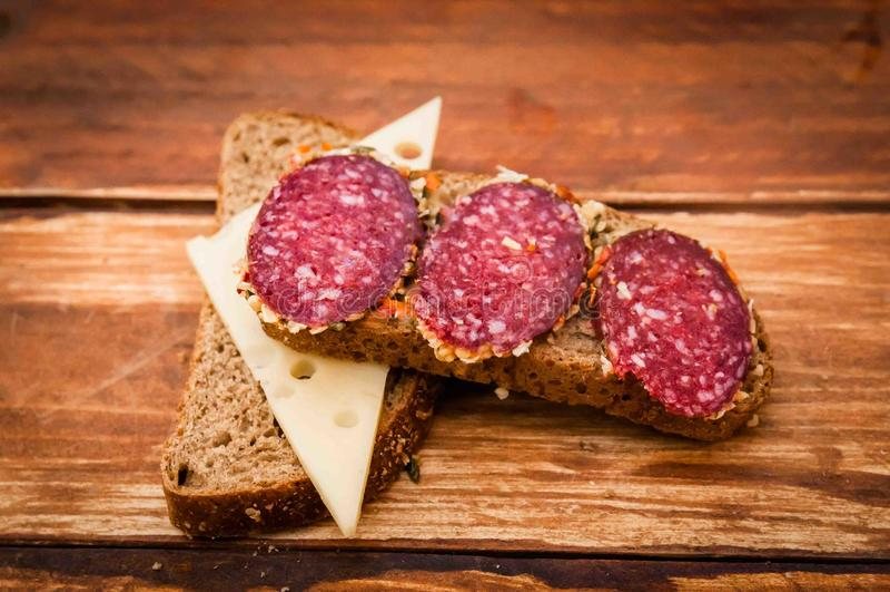 La salsiccia ha cucinato la salsiccia affumicata, formaggio con buio per la prima colazione, panino, pane nero, aglio, pepe nero, fotografia stock libera da diritti