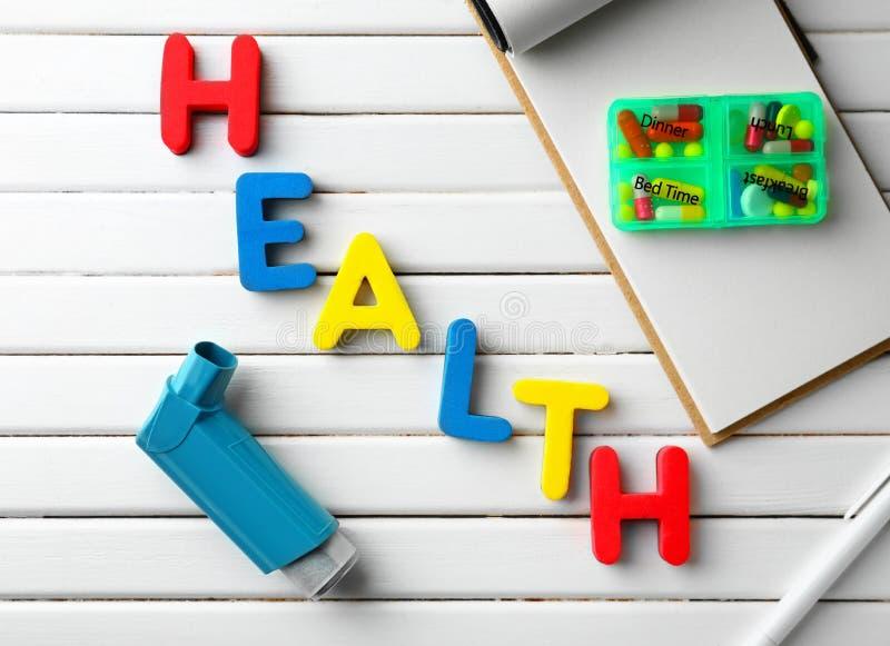La SALUD de la palabra hizo de letras del color con el inhalador del asma y de píldoras en el fondo de madera blanco foto de archivo libre de regalías