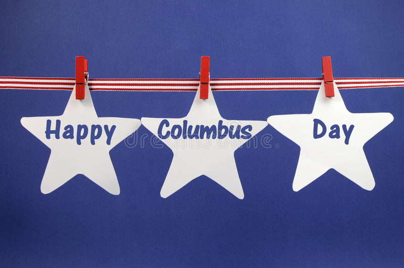 La salutation heureuse de message de Columbus Day écrite à travers l'étoile blanche carde pendre du ruban et des chevilles de rayu photographie stock