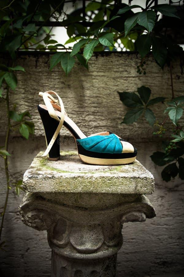 La sandalia del tacón alto en columna adentro gaden día de verano imagenes de archivo