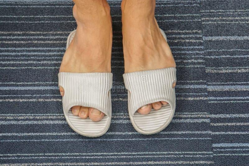 La sandalia es demasiado apretada para que los pies del ` s de los hombres consigan en imágenes de archivo libres de regalías