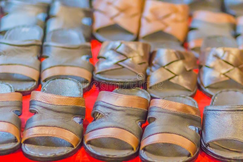La sandalia y el calzado del zapato de cuero para la venta en el estante en el mercado de pulgas hacen compras fotografía de archivo