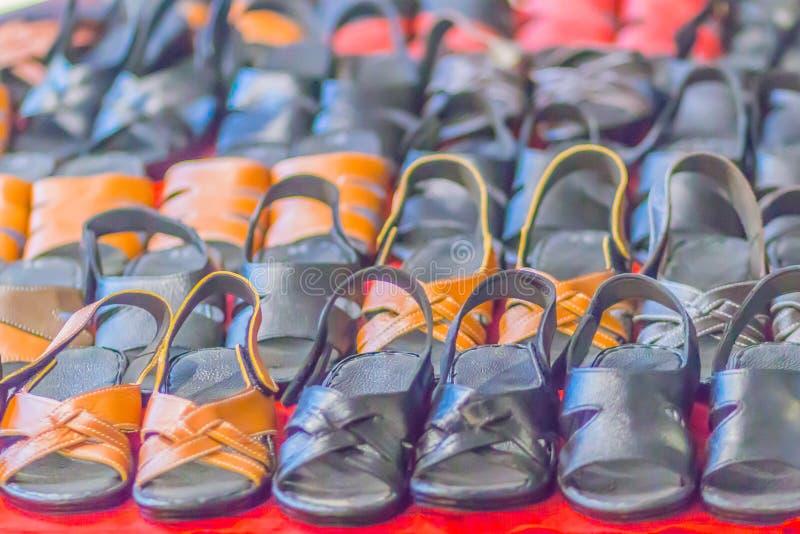 La sandalia y el calzado del zapato de cuero para la venta en el estante en el mercado de pulgas hacen compras fotografía de archivo libre de regalías