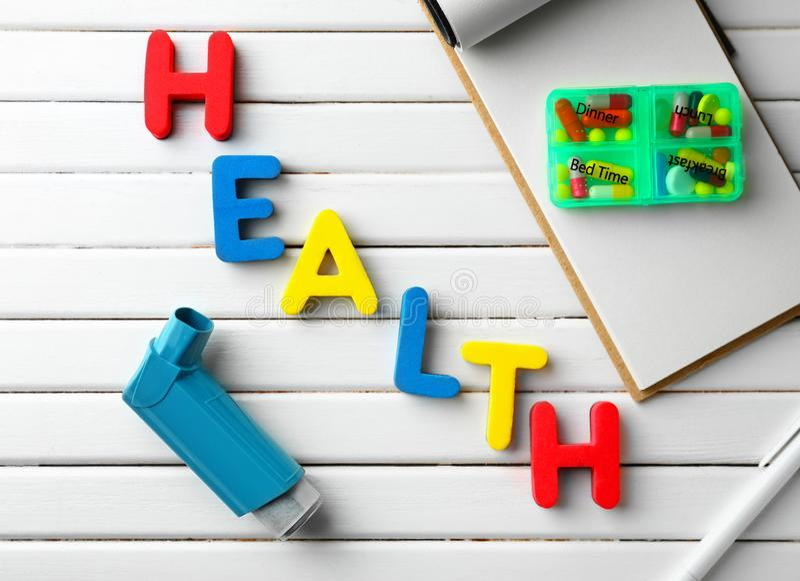 La SANTÉ de Word a fait des lettres de couleur avec l'inhalateur d'asthme et des pilules sur le fond en bois blanc photo libre de droits