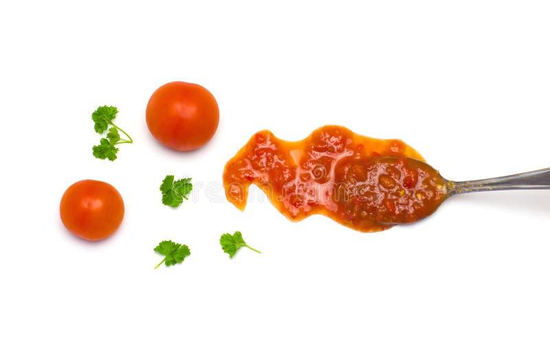 La sauce et les tomates ont débordé une cuillère à côté des tomates et des feuilles de persil photographie stock libre de droits