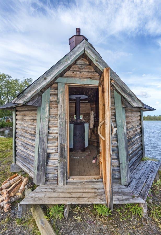 La sauna de madera sueca con la puerta abierta, el woodstove se considera en interieur, el agua del lago Gaxsjon está en el fondo fotografía de archivo libre de regalías