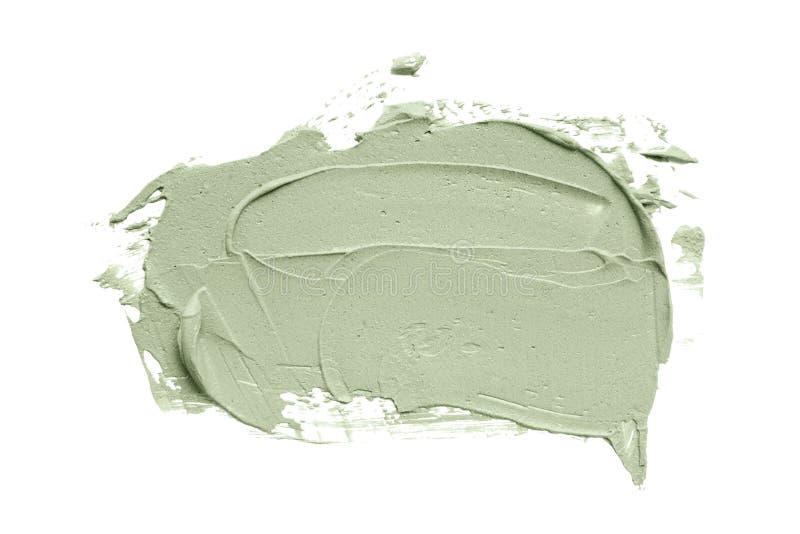 La sbavatura facciale della maschera dell'argilla blu su bianco ha isolato il fondo immagini stock