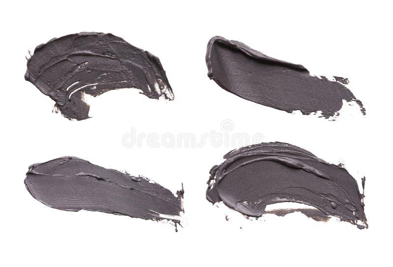 La sbavatura facciale della maschera dell'argilla blu su bianco ha isolato il fondo immagine stock