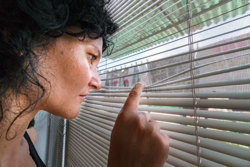 La sbirciata emozionante della donna cerca il giorno fuori sopra i ciechi di finestra immagine stock libera da diritti