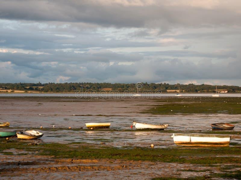 La scène d'estuaire dans le manningtree avec la marée amarrée de bateaux opacifie des terres photos stock