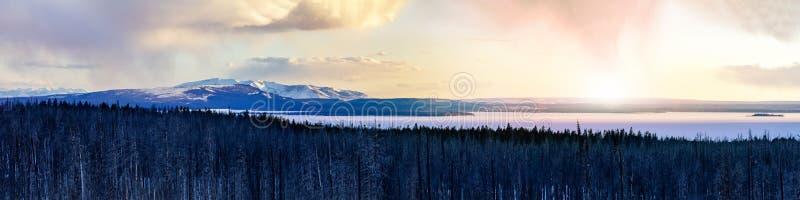 La scène de paysage d'hiver en parc national de Yellowstone avec la lueur chaude de la lumière du soleil derrière la neige a couv image stock