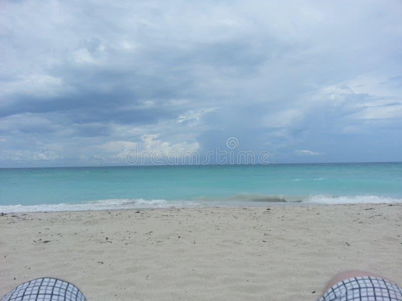 La scène vide de plage avec les nuages foncés soutiennent dedans photos libres de droits