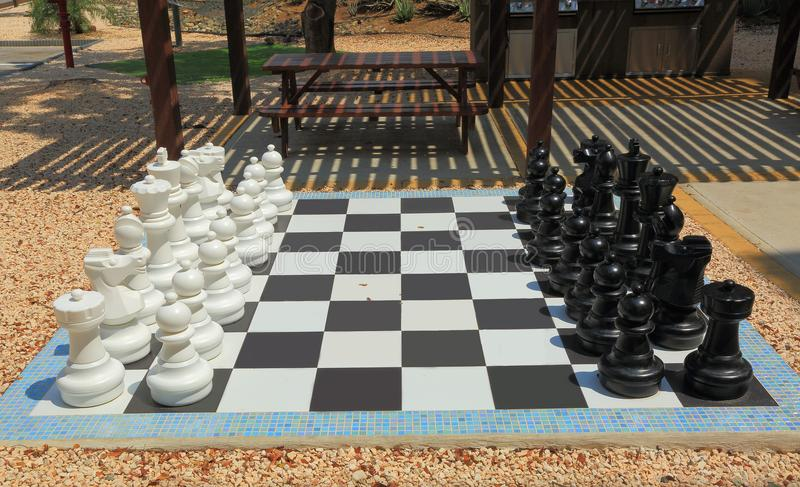 La scacchiera con scacchi in bianco e nero enormi calcola per il gioco all'aperto Ambiti di provenienza piacevoli fotografia stock libera da diritti