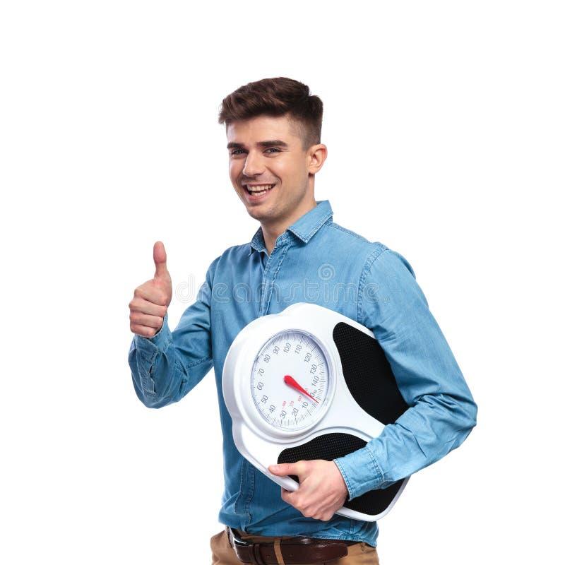 La scala casuale della tenuta dell'uomo di misura felice e fa il segno giusto immagini stock libere da diritti