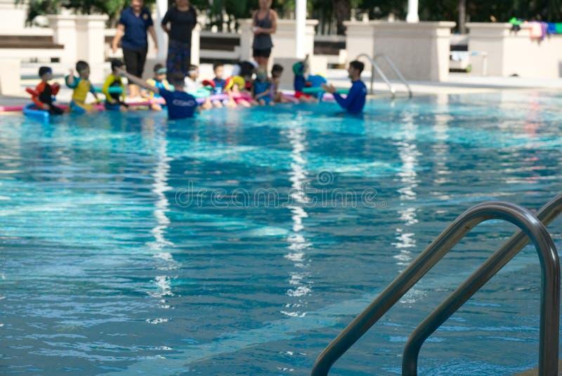 La scala della piscina sulla foto della sfuocatura scherza il nuoto di pratica con il TR immagini stock libere da diritti