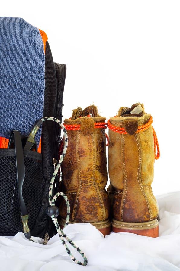 La scarpa di cuoio e il knapsage per l'avventura viaggiano su bianco immagini stock