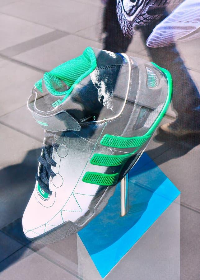 La scarpa di sport di Adidas ha visualizzato in una finestra con la riflessione di vetro, Pechino, Cina fotografia stock