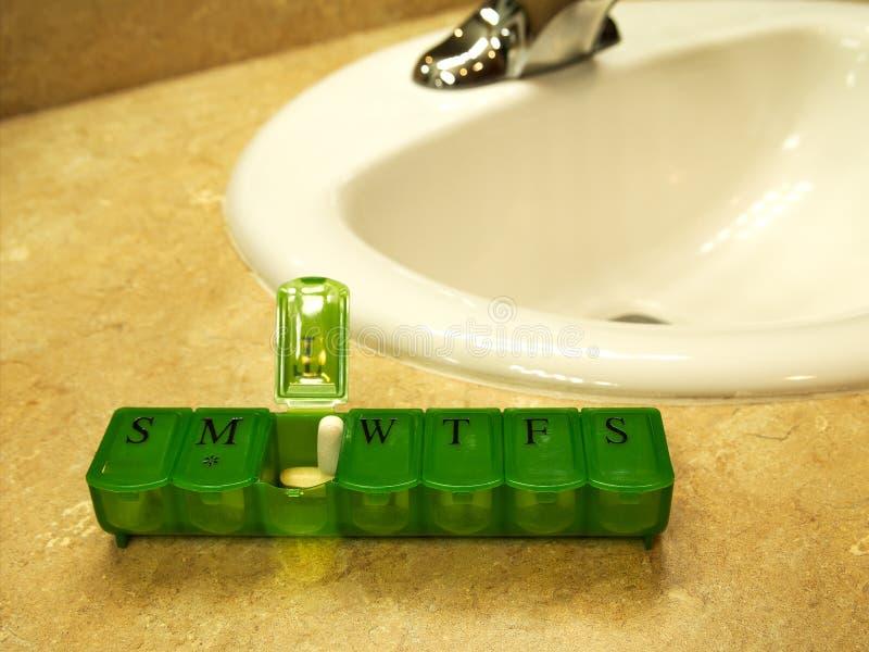 La scatola verde di sette giorni della pillola con le pillole si siede sul controsoffitto fotografie stock libere da diritti