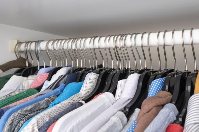 La scelta dei vestiti dei colori differenti appende sui ganci immagini stock libere da diritti