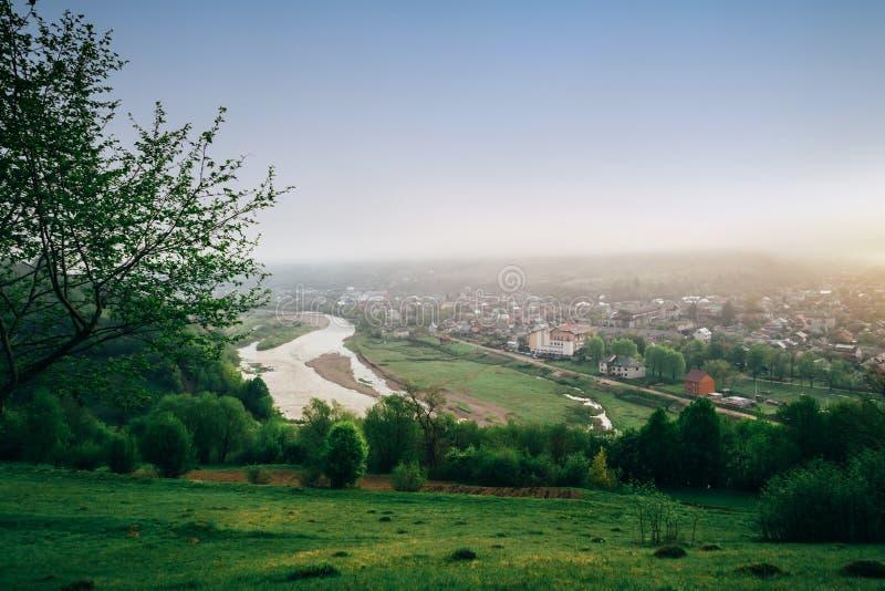 La scena all'aperto pittoresca sulla valle della montagna, il fiume ed il piccolo villaggio nella mattina annebbiano all'alba Pos fotografia stock