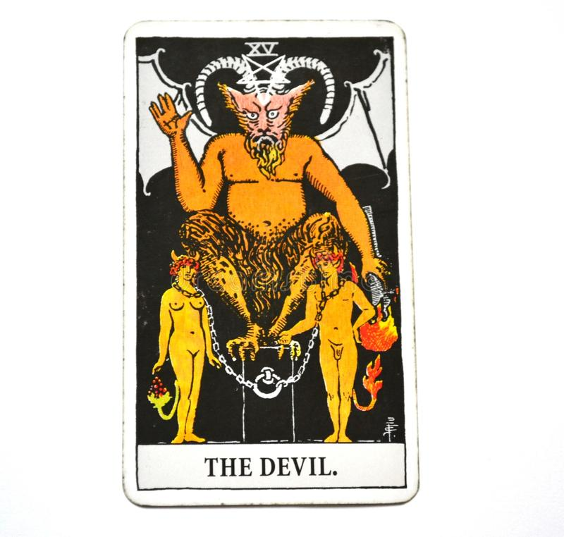 La schiavitù della carta di tarocchi del diavolo, tentazione, asservimento, materialismo, bianco Bachground di dipendenze fotografie stock