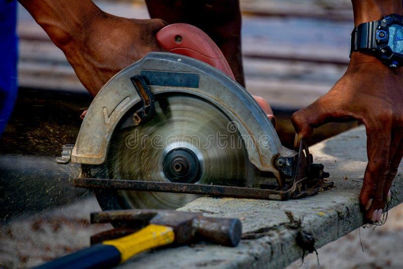 La scie circulaire portative électrique d'utilisation d'homme coupe un vieux rondin photo libre de droits