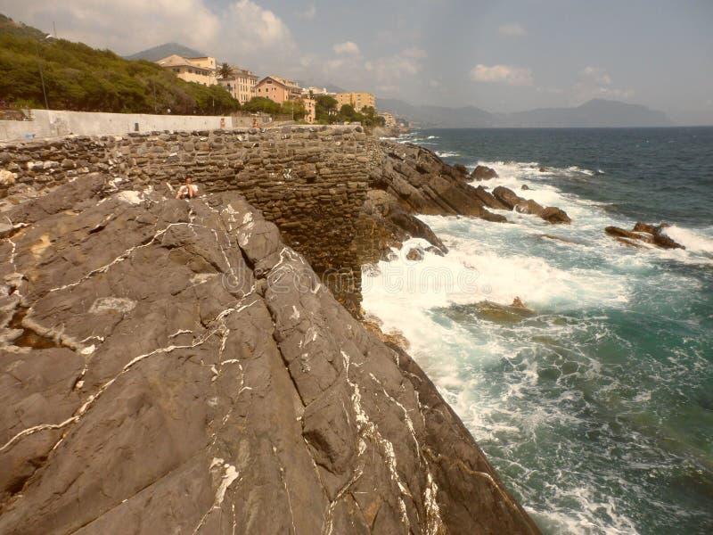 La scogliera e le onde che si schiantano su nei mari di Genova immagine stock