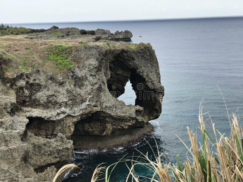La scogliera eccezionale e una vista di abbagliamento dell'oceano verde smeraldo a capo Manzamo nel Giappone immagini stock