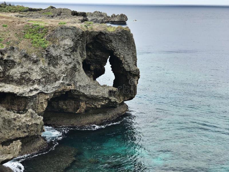 La scogliera eccezionale e una vista di abbagliamento dell'oceano verde smeraldo a capo Manzamo nel Giappone fotografia stock libera da diritti