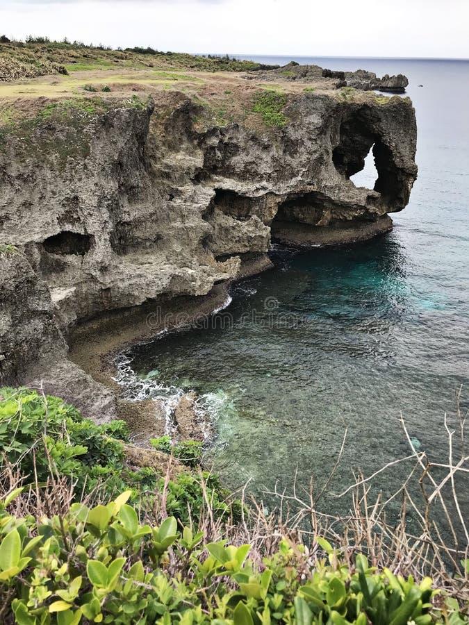 La scogliera eccezionale e una vista di abbagliamento dell'oceano verde smeraldo a capo Manzamo nel Giappone fotografie stock libere da diritti