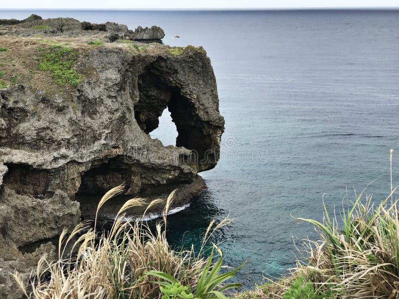 La scogliera eccezionale e una vista di abbagliamento dell'oceano verde smeraldo a capo Manzamo nel Giappone fotografia stock