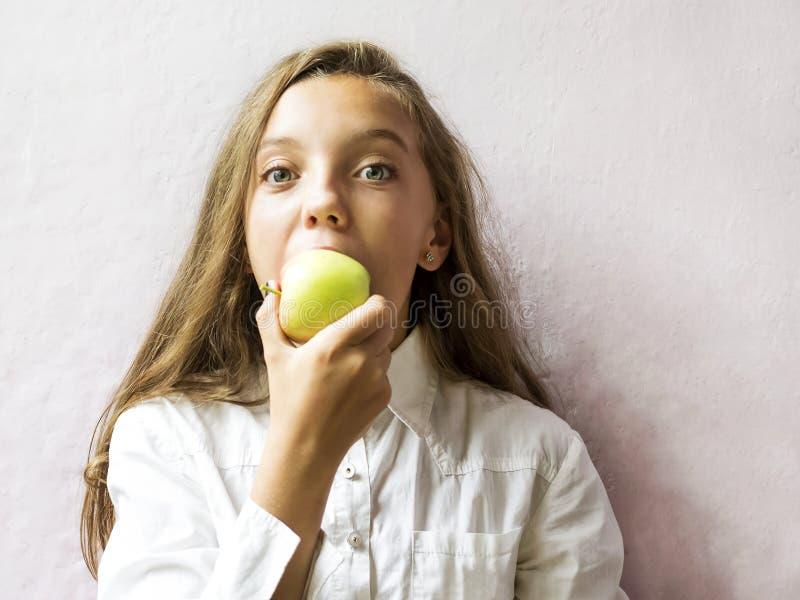 La scolara bionda sveglia della ragazza morde una mela verde Alimento sano fotografie stock