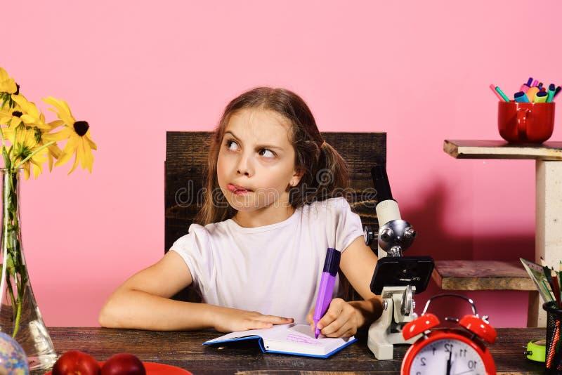 La scolara con il fronte interrogante scrive in taccuino immagine stock libera da diritti