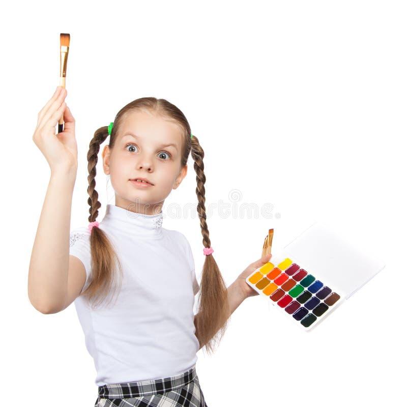 La scolara divertente sveglia della ragazza tiene la pittura dell'acquerello La nappa ha alzato i suoi occhi spalancati fotografia stock