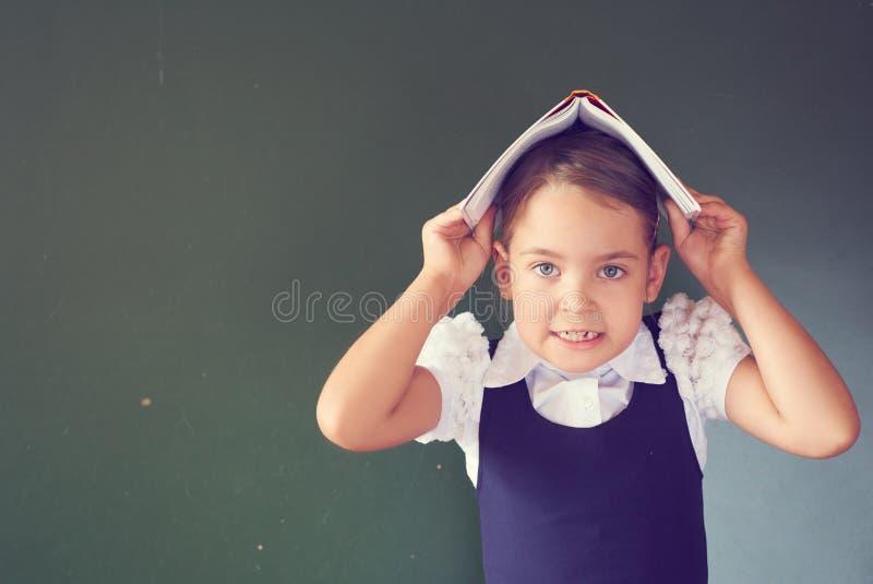 La scolara graziosa in un vestito dalla scuola sta tenente un libro aperto sulla sua testa vicino alla lavagna fotografie stock