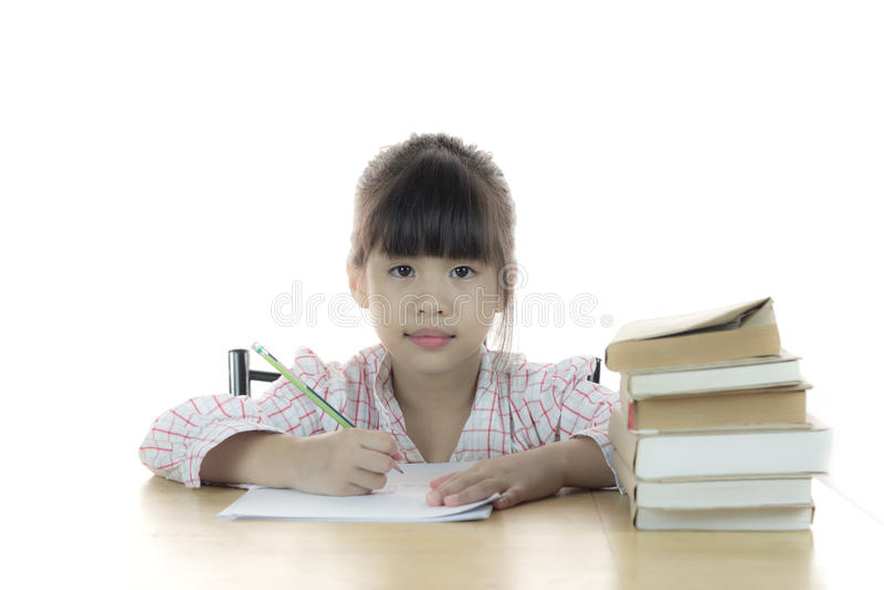 La scolara lavora al suo compito fotografia stock