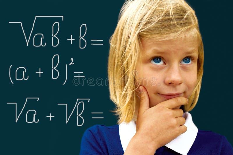 La scolara riflette la soluzione del problema matematico immagine stock libera da diritti