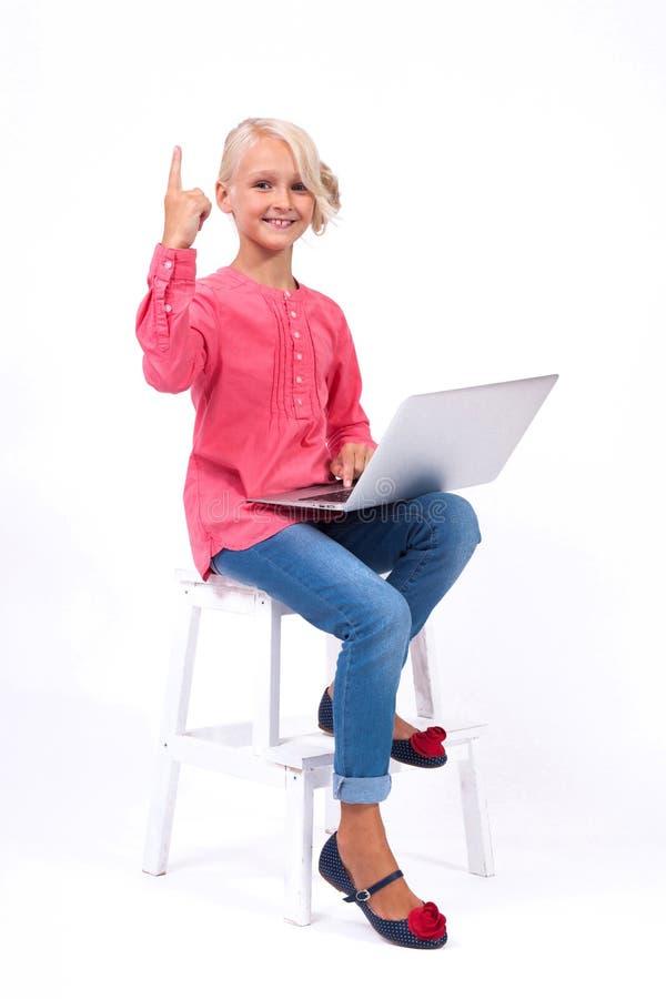 La scolara sorridente impara e comunica con l'aiuto del modo fotografia stock