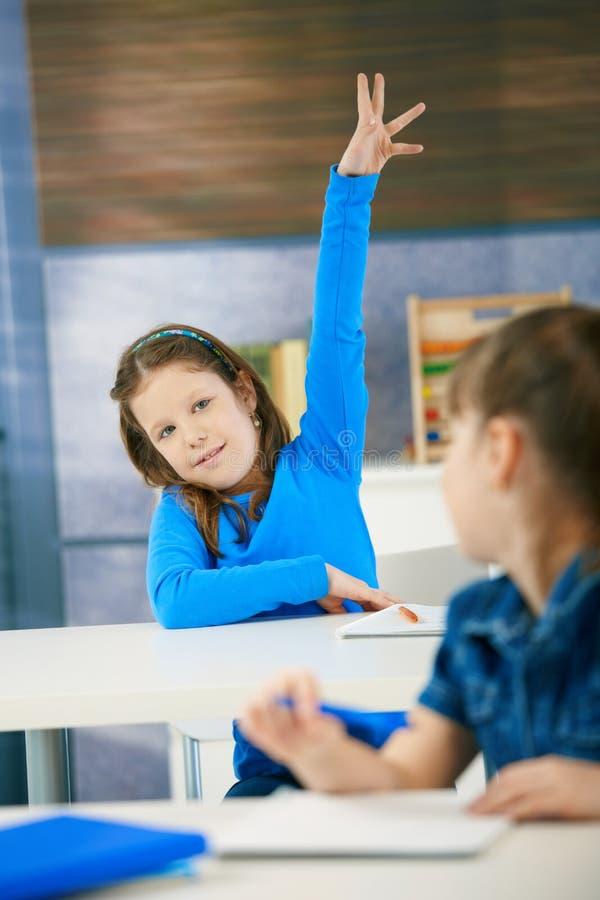 La scolara sorridente solleva la mano immagini stock