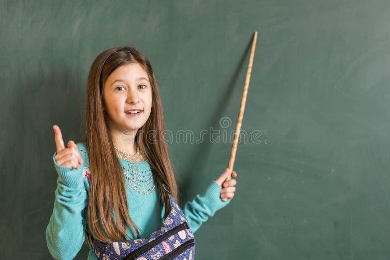 La scolara sta alla lavagna con un puntatore Scolaro con il puntatore, la lavagna di sbirciata della ragazza del bambino, l'appre immagini stock libere da diritti