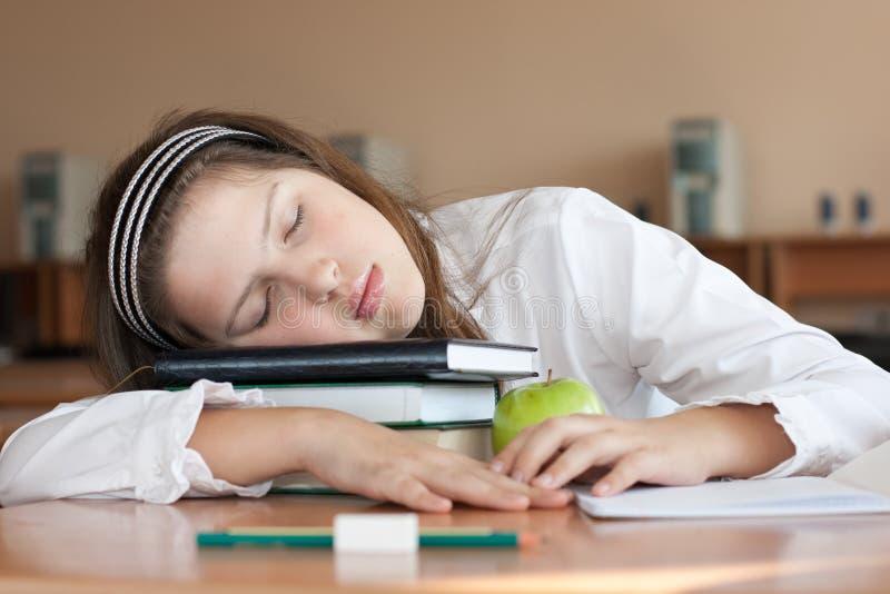 La scolara sta dormendo con i suoi libri alla lezione fotografia stock