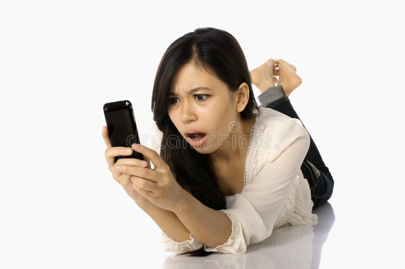 La scossa asiatica della donna vede il suo cellulare immagine stock
