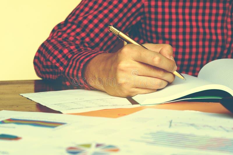 La scrittura dell'uomo di affari fa la nota circa le spese ed il pensiero con fotografie stock libere da diritti