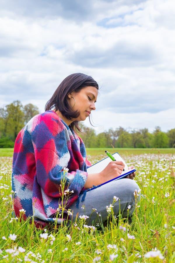 La scrittura della donna nel prato di fioritura con la molla fiorisce fotografia stock libera da diritti