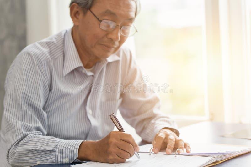 La scrittura di lavoro senior asiatica della mano o firma il contratto assicurativo fotografie stock libere da diritti