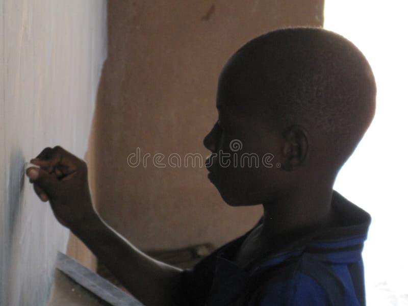 La scrittura non identificata del bambino sulla lavagna nella carità dirige la scuola, Burkina Faso fotografia stock libera da diritti