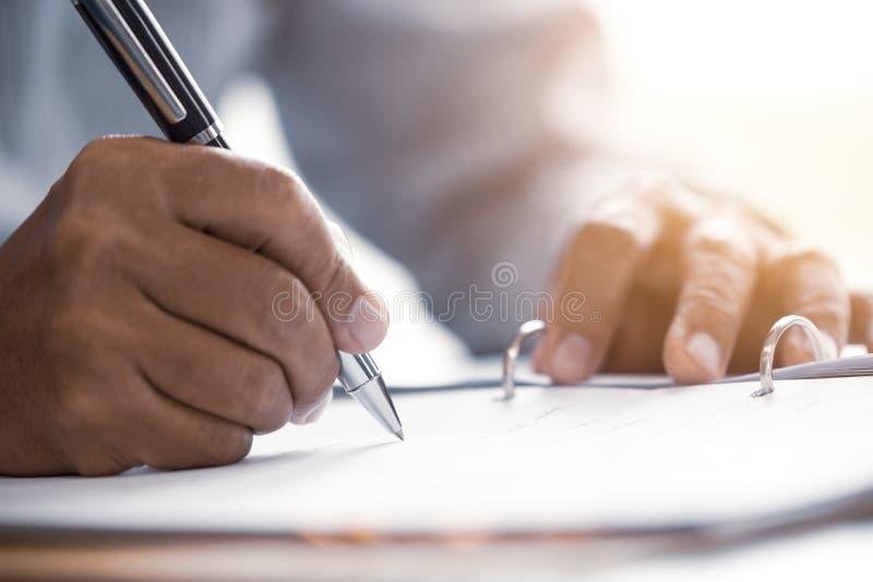 La scrittura senior maschio della mano del primo piano firma il contratto immagini stock