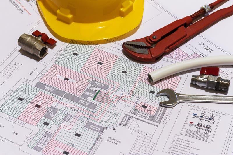 La scrivania con i montaggi idraulici, il casco ed il pavimento radiante progettano immagini stock libere da diritti
